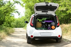 Car with camping equipment in trunk on forest road. Space for text