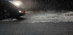 Car with headlights run through flood water after hard rain fall at night.