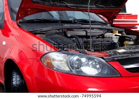 Car with open hood in auto repair shop.