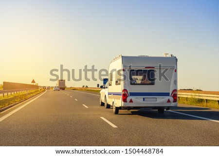 Car with recreational vehicle motor home trailer on highway. Family vacation trip concept. #1504468784