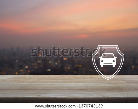 Car with shield flat icon on wooden table over blur of cityscape on warm light sundown, Business automobile insurance concept #1370743139