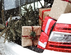 Car with trunk full of gift boxes, presents and fir tree for Christmas. Car, presents, craft box, snow, holidays. Street outdoor.