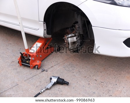 Car without tire at jack in service