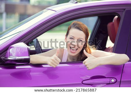 Car. Woman driver happy smiling showing thumbs up coming out of violet car side window on outside parking lot background. Beautiful young woman happy with her new vehicle. Positive face expression