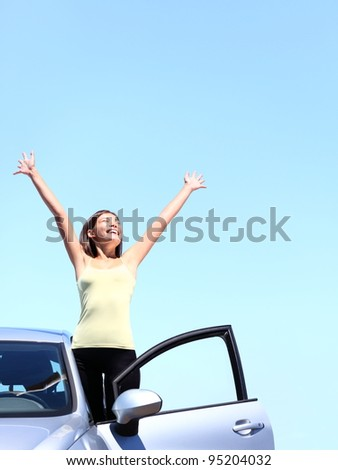 Car woman happy freedom concept. Cheering young woman with arms raised stepping out of new car under blue sky. Beautiful young multiracial Asian / Caucasian female model free.