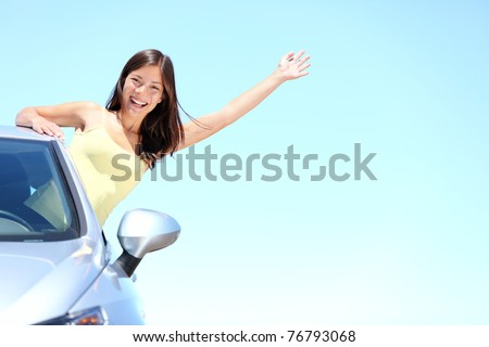 Car woman on road on road trip waving happy smiling out the window. Asian Caucasian girl on summer holidays above the clouds. - stock photo
