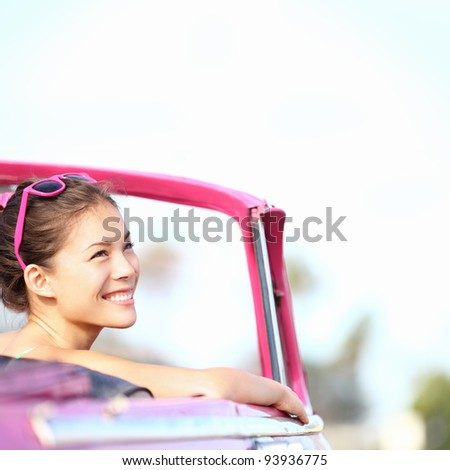 Car woman smiling happy enjoying car road trip travel vacation. Young retro woman in pink vintage convertible car looking to side. Beautiful young multiracial caucasian / chinese asian in Havana, Cuba - stock photo
