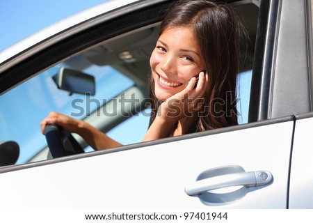 Car woman using smart phone while driving in car. Beautiful young woman talking on mobile phone smiling happy looking at camera. Mixed race eurasian woman.