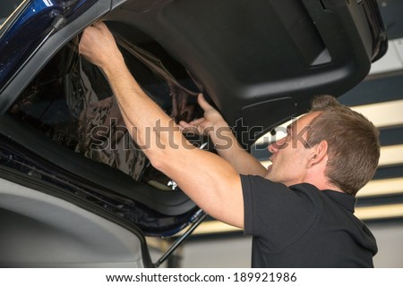 Car wrapping specialist attaching tinting foil to car window #189921986