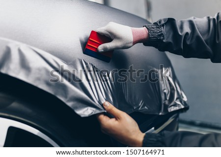 Car wrapping specialist putting vinyl foil or film on car. Selective focus.  Foto stock ©