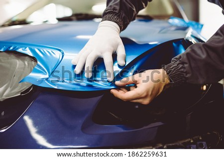 Car wrapping specialist putting vinyl foil or film on car. Selective focus.  Stock photo ©