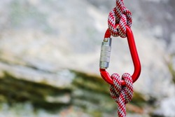 carabiner with rope on rocky background