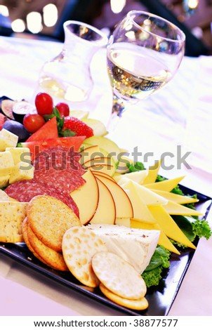 Carafe and glass of white wine with cheeseboard assortment