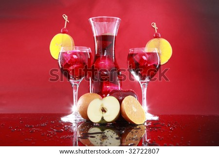 Carafe and sangria or fruit punch glasses wedged with an orange slice and maraschino cherry