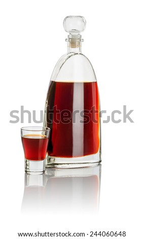 Carafe and shot glass filled with brown liquid