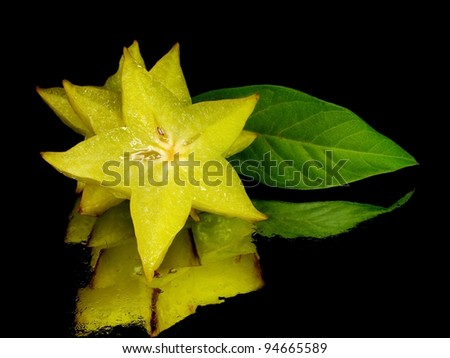 carambola - starfruit on a black background with water drops