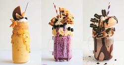 Caramel and chocolate indulgent extreme milkshakes with brezel waffles, popcorn, marshmallow, ice cream and whipped cream. Crazy freakshake food trend.