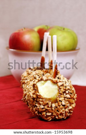 caramel and nut covered apple with another bowl of apples behind it.  Shallow depth of field with focus on foreground apple
