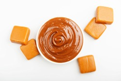 Caramel candies and caramel topping  on a white background.