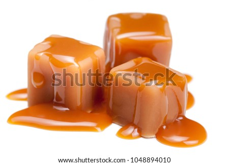 Caramel candies with caramel sauce isolated on a white background close up.