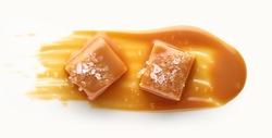 Caramel candy with salt and sweet sauce top view isolated on white background