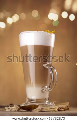 caramel coffee latte with lights on background in a tall glass, shallow dof