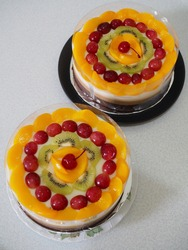 caramel - combination pudding with different flavour every layer, milk, caramel and chocolate. with various fruits as topping. gritty, grainy and shiny textured with blurry background