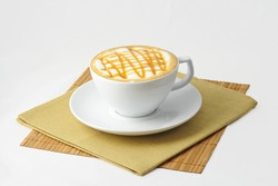 Caramel macchiato or cappuccino with caramel topping and foam caffeine in tea cup or mug with napkins isolated on white background for illustration and design of menu bar restaurant edition