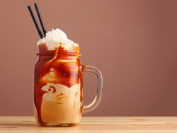 caramel milkshake with coffee on wooden table. Salted caramel ice cream sundae. Cold coffee drink frappe frappuccino , with whipped cream