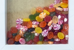 Caramel multicolored lollipops in a large box. Sweet dessert