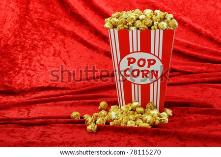 caramel popcorn in a decorative red and white popcorn cup on a red velvet background