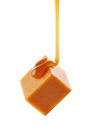 caramel sauce flowing on flying caramel candy isolated on white background