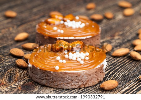 caramel tartlet with milk cheese filling and lots of salted caramel with nuts, almonds on tartlets with cottage cheese or butter cream and caramel
