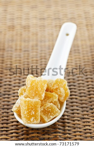 Caramelized ginger candy pieces on white spoon