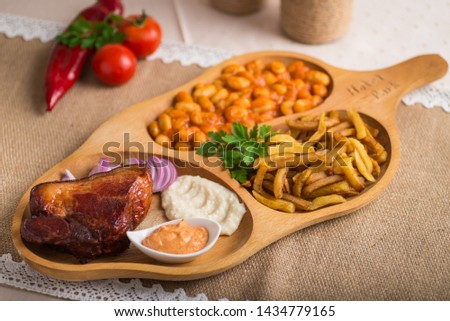 Caramelized pork chops on  a wooden plate potato fries and beans