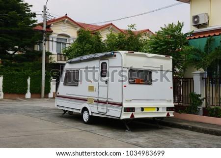Caravan car in the city, car tourist trailer #1034983699