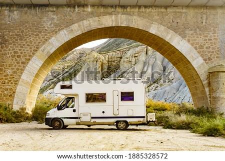 Caravan in Tabernas desert camping near road arch bridge, Almeria Spain. Traveling with motorhome. Stockfoto ©