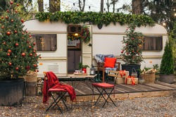Caravan mobile home with terrace, Mobile home decorated with Christmas decor. Festive atmosphere - lights, red blankets, Christmas trees. Caravan camping. mobile home trailer. Selective focus