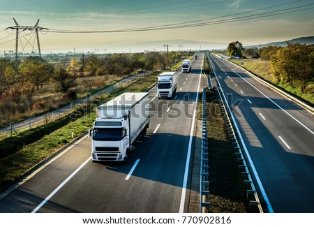 Caravan of white trucks in line on country highway #770902816