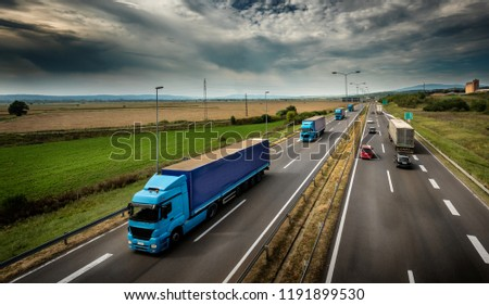 Caravan or convoy of Blue Lorry  trucks in line on a country highway #1191899530