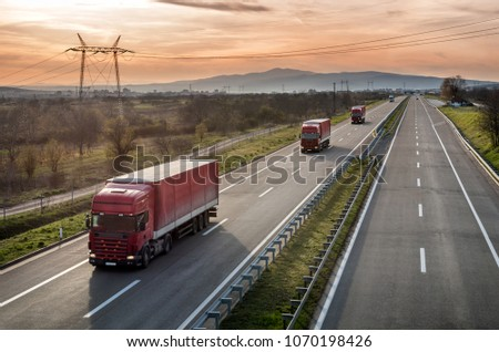 Caravan or convoy of Red Lorry trucks in line on a country highway