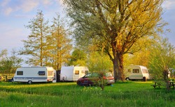 Caravan trailer and a car parked on a green lawn in a camping site. Idyllic spring landscape. Holland. RV, transportation, road trip, vacations, ecotourism, travel, lifestyle, recreation