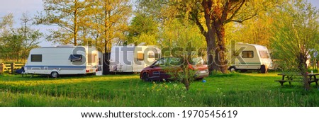 Caravan trailer and a car parked on a green lawn in a camping site. Idyllic spring landscape. Holland. RV, transportation, road trip, vacations, ecotourism, travel, lifestyle, recreation Stock photo ©
