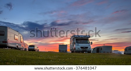 Caravans and cars parked on a grassy campground in summer under beautiful sunset #376481047