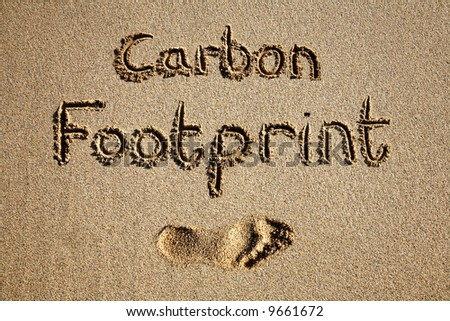 Carbon footprint written in sand on a beach.