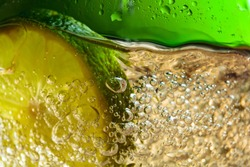 Carbonated drink or cocktail with lime, abstract splashing. Macro shot.