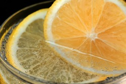 Carbonated lemonade with lemon in a transparent glass close-up macro photography