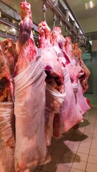 Carcasses of beef hang on hooks.Meat industry,Meats hanging in the cold store.Peeled cow hanging in the hook at the butcher shop