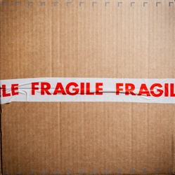 Card board box sealed with red and white fragile packing tape