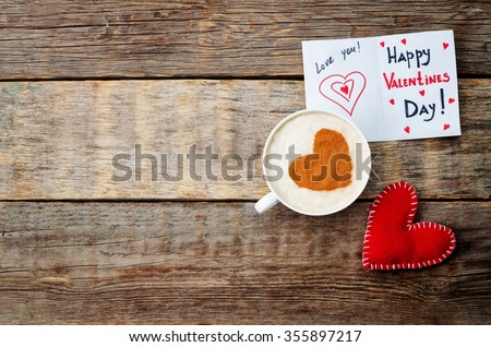 card for Valentines day, red toy heart and a cup of coffee on a dark wood background. toning. selective Focus #355897217